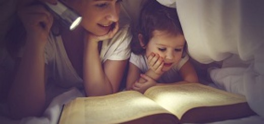 Family reading bedtime. Mom and child reading book with a flashlight under blanket